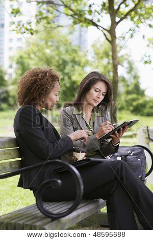 Dos jóvenes empresarias trabajando en un banco del parque