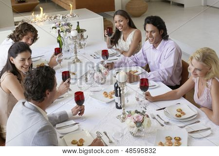 Group of multiethnic friends drinking and socialising at dinner party