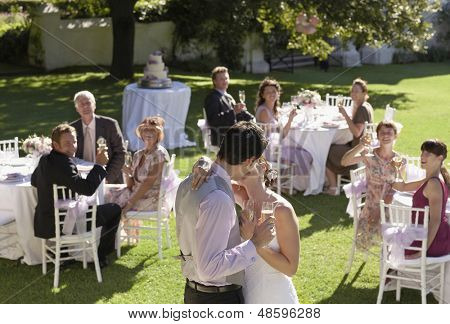 Young bride and groom kissing while wedding guests toasting champagne flutes in garden