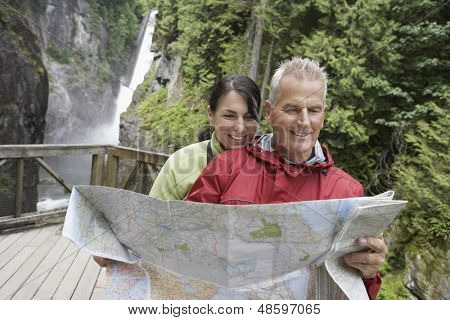 Mature man and woman reading map with waterfall in the background