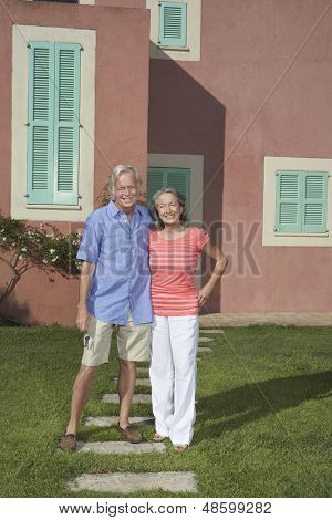 Full length portrait of a senior couple standing in front of house