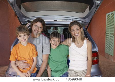 Portrait of a happy couple with two sons sitting on car tailgate