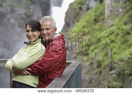 Portret van een glimlachende midden leeftijd paar tegen reling in Bergen