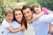 stock photo of piggyback ride  - Portrait of happy family with young kids - JPG