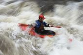 image of canoe boat man  - Side view of a blurred man kayaking in rough river - JPG