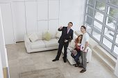 Elevated full length view of a male real estate agent showing couple new home