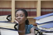 stock photo of dreadlock  - Closeup of a female office worker sitting behind stacks of documents in office - JPG