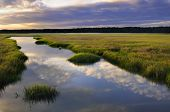 stock photo of inlet  - Early morning sun lighting clouds along ocean inlet - JPG