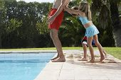 Side view of two children pushing cropped father into swimming pool