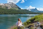 stock photo of engadine  - girl on the shore of a mountain lake - JPG