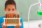 stock photo of schoolboys  - cute male primary school student in science class holding tubes - JPG