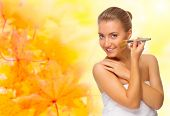 Healthy girl with makeup brush on autumnal background