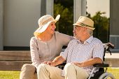 picture of crippled  - Senior disabled man and wife talking outdoors in park - JPG