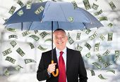 Happy man holding an umbrella in a money rain