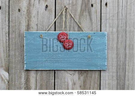 Antique blue sign with cherry soda bottle caps hanging on door