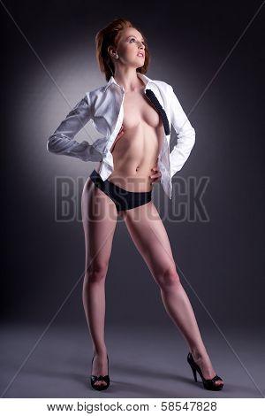 Leggy slim model posing in unbuttoned white blouse