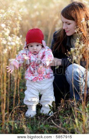 junge Mutter mit Baby auf einer Wiese