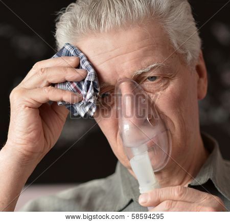 An old man doing inhalation