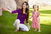 picture of babysitter  - Beautiful young Hispanic mother and her baby girl having fun with bubbles outdoors - JPG