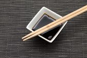 stock photo of soy sauce  - A traditinonal dark soy sauce with chopsticks
