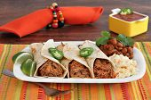 stock photo of jalapeno  - Three pulled pork burritos carnitas with a side of slaw and chili beans - JPG