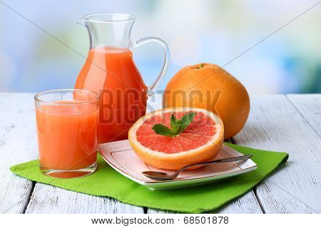 Half of grapefruit, glass jug with fresh juice and spoon on plate on light background