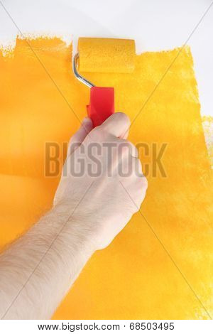 Roller brush with yellow paint in hand closeup