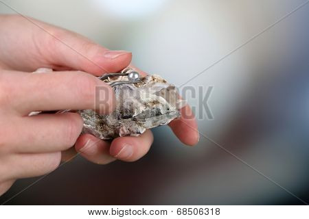 Hand with tweezers holding pearl and oyster on mature background