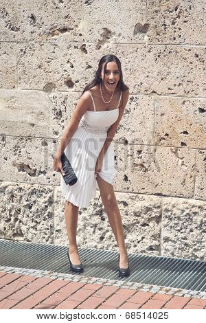 Candid image of a laughing vivacious elegant young woman in a white summer dress and high heels carrying a clutch purse standing in front of an old stone building