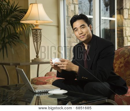 Young Businessman At Laptop Holding A Coffee Cup