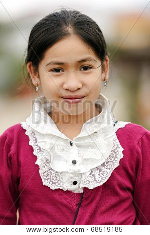 VANG VIENG, LAOS, MARCH 18, 2011: Portrait of a Laotian little girl wearing traditional clothes in the village of Vang Vieng in Laos.