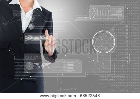 Businesswoman pointing at interface against grey vignette