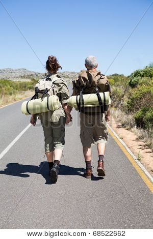 Hitch hiking couple holding hands on the road on a sunny day