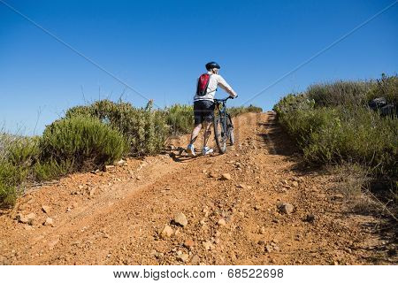 Fit cyclist pushing bike uphill on country terrain on a sunny day