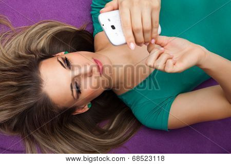 Woman Sending A Text Lying On A Bed At Home