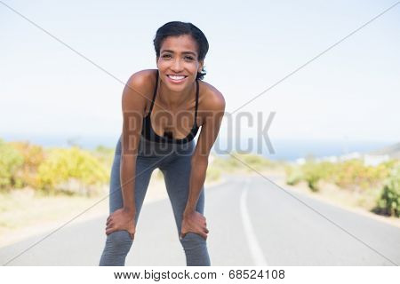 Fit woman taking a break on the open road on a sunny day in the countryside