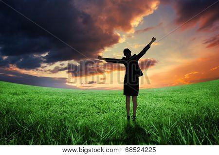 Excited businesswoman cheering against green field under orange sky