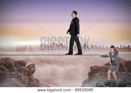 Young businesswoman pulling a tightrope for businessman against cityscape on the horizon