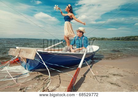 Romantic young couple cuddling in rowboat at lake