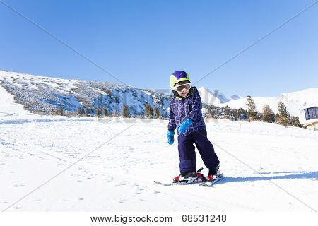 Kid in ski mask skiing on snow downhill