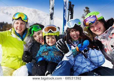 Positive friends with kid together wear ski masks