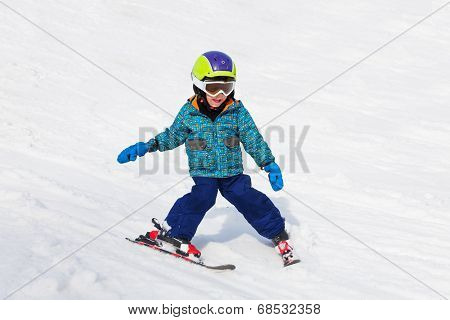 Smiling boy in ski mask learns skiing
