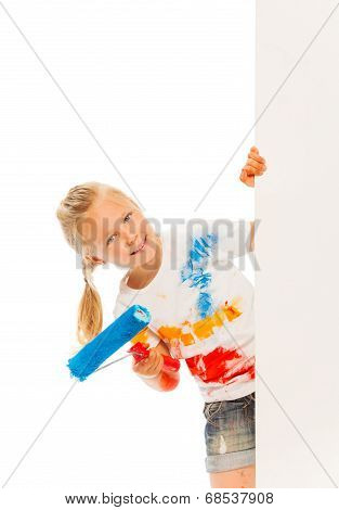 Little Caucasian girl leans out of wall