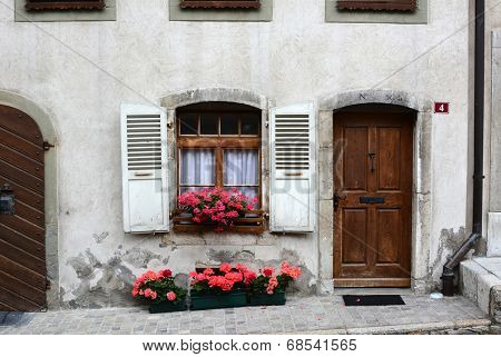 GRUYERES, SWITZERLAND - JULY 8, 2014: Front door on traditional Swiss home. The picturesque  home is on the cobblestone main street in old town Gruyeres leading to the castle and church.