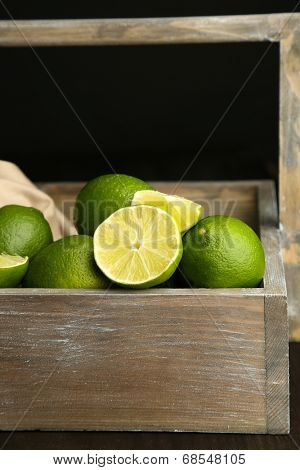 Fresh juicy limes in wooden crate, on dark background