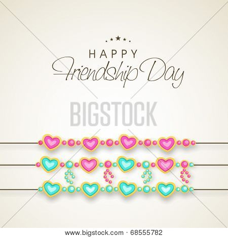 Happy Friendship Day celebrations concept with heart shape decorated band on shiny brown background.