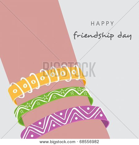 Happy Friendship Day celebrations concept with colorful wristbands on grey background.