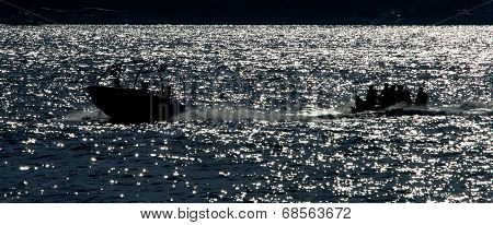Backlit speedboat pulling inflatable banana at sea