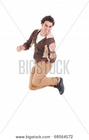 Portrait Of Ecstatic Casual Young Man Jumping With Hands Raised