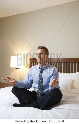 Businessman Meditating On Bed